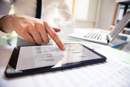 Close-up Of A Businessperson's Hand Analyzing Bill On Digital Tablet Over Desk Foto de archivo