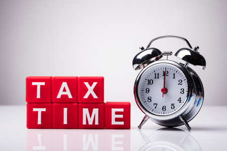 Red Cubic Blocks With Tax Time Word Near Alarm Clock On Reflective Background