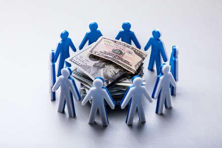 Gestapelte Banknoten, umgeben von menschlichen Figuren, isoliert auf weißem Hintergrund