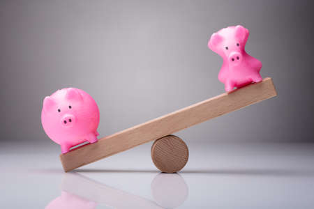 Unbalance Of Two Piggybanks On Wooden Seesaw Against Gray Background