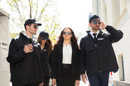 Portrait Of Young Female Celebrity With Bodyguards Walking On Sidewalk 스톡 콘텐츠