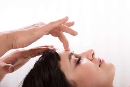 Close-up de una tranquila joven recibiendo tratamiento de Reiki en el spa
