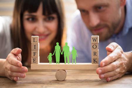 Glückliches Paar, das Balance zwischen Arbeit und Leben mit Familienpapier schützt, das auf Wippe herausgeschnitten wird