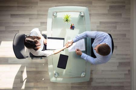 Verhoogde weergave van zakenman hand schudden met vrouwelijke aanvrager op de werkplek