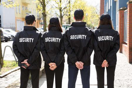 Rückansicht der Sicherheitskräfte mit den Händen hinter dem Rücken, die in einer Reihe stehen