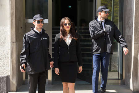Young Businesswoman Stepping Out From Office Building With Her Bodyguards