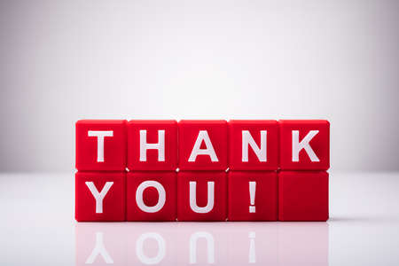 Red Cubic Blocks With Thank You Text On Reflective Background Stock Photo