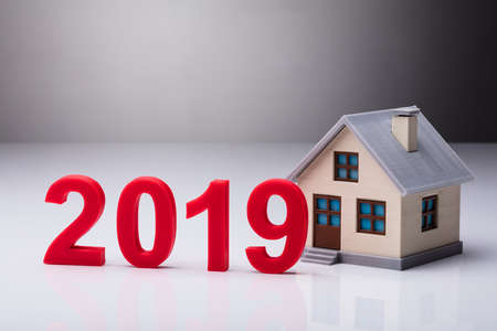 Year 2019 Besides House Model On Reflective Background