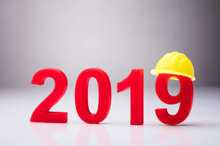 Year 2019 With Yellow Hardhat Over White Background Standard-Bild - 103283405