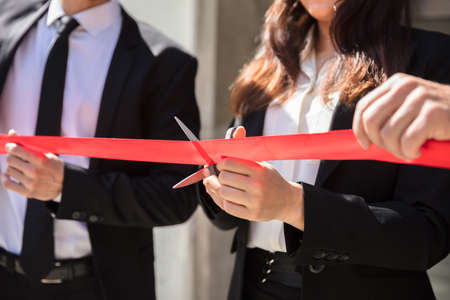 Close-up Of Businesspeople Hand Cutting Red Ribbon With Scissors
