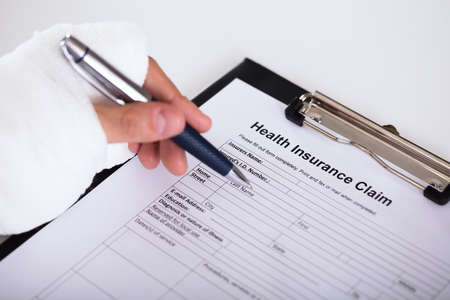 Close-up Of A Person With Fractured Hand Filling Medical Benefit Claim Form Banque d'images