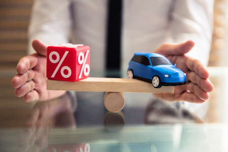 Businessperson's Hand Protecting Balance Between Cubic Block With Percentage Symbol And Blue Car Stockfoto