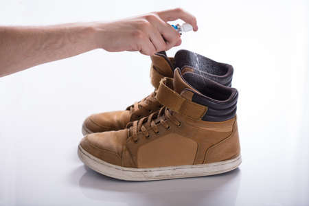 Man's Hand Spreading Deodorant On Smelly Shoes Against White Background