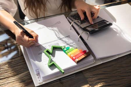 Vrouw berekening van factuur met energie-efficiënte grafiek en huis silhouet In Office Stockfoto