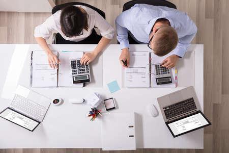 Dos jóvenes empresarios calcular la factura con la calculadora Foto de archivo