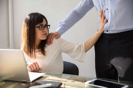 Young Woman Defending Herself From Sexual Harassment By Boss At Workplace