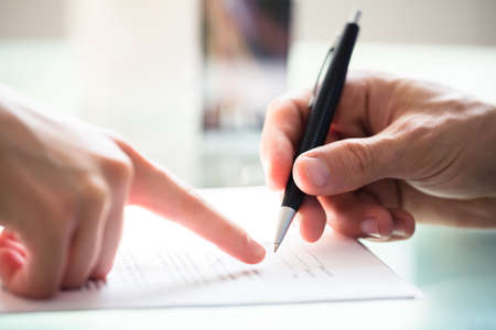 Close-up Of Businessperson's Hand Assisting Employee While Signing Document