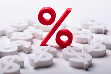 Rotes Prozent-Symbol, umgeben von Dollarzeichen Standard-Bild