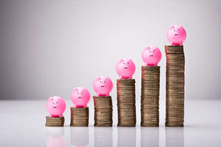 Close-up Pink Piggybank On Increasing Stacked Coins Against White Background