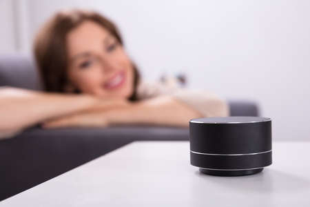 Woman Listening To Black Wireless Speaker On Furniture Archivio Fotografico