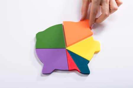 Businesswomans Hand Placing Last Orange Piece Into Multi Colored Piggybank On White Background