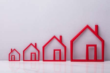 Increasing Outline Of Red Houses Against White Background Stock Photo