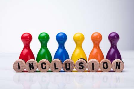 Sughero in legno con testo di inclusione davanti al pedone multicolore su sfondo riflettente