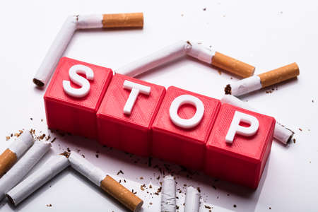 Red Stop Cubic Blocks Surrounded By Broken Cigarettes On White Background