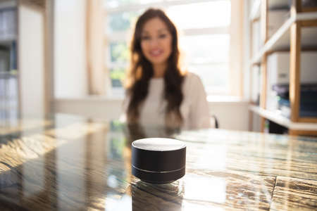 Close-up Of Wireless Speaker In Front Of Businesswoman Listening To Music 스톡 콘텐츠