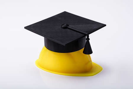 Close-up Of Graduation Hat On Yellow Hardhat Over White Background