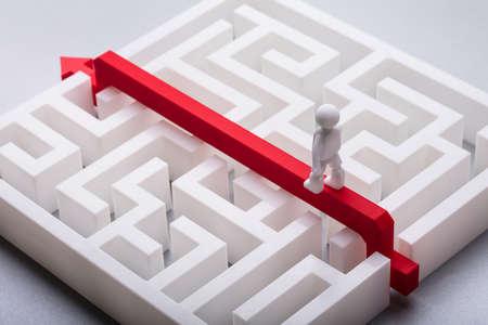 Primo piano della figura umana che attraversa il labirinto bianco sopra la freccia rossa