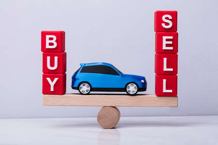 Blue Car Between And Buy And Sell Cubic Blocks Balancing On Wooden Seesaw Banque d'images - 104194512