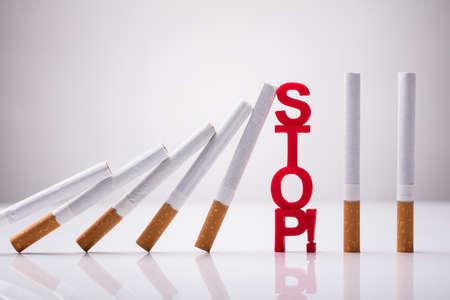 Fallende Zigaretten gestoppt durch Stoppwort vor weißem Hintergrund