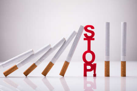 Falling Cigarettes Stopped By Stop Word Against White Background