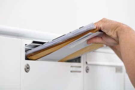 Primo piano della mano di un uomo che inserisce le lettere nella cassetta postale