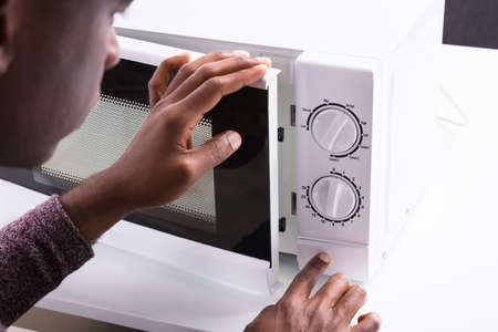 Close-up Of A Man Pressing Button Of Microwave Oven