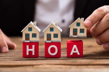 De hand die van de ondernemer huismodel over rode blokken HOA op houten bureau plaatsen