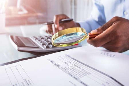 Primo Piano Di Un Uomo D'affari Che Tiene Lente D'ingrandimento Sulla Fattura Utilizzando La Calcolatrice
