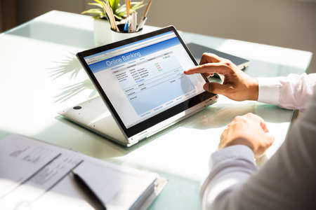 Close-up of a businessman's hand doing online banking on laptop over glass desk
