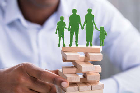 Close-up Of A Person Holding Blocks With Green Family Figures On Top Stock Photo