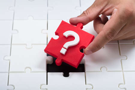 Close-up of a person's hand placing red question mark piece into jigsaw puzzle