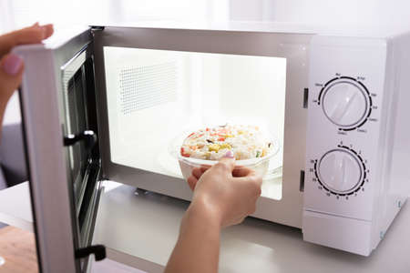 Close-up Of A Woman's Hand Heating Food In Microwave Oven