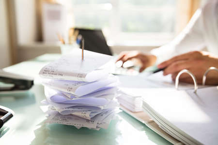 Close-up of stacked receipts in paper nail at workplace