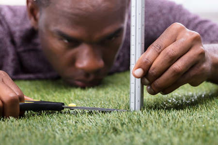 Close-up Of A Man Cutting Green Grass Measured With Ruler Stock Photo