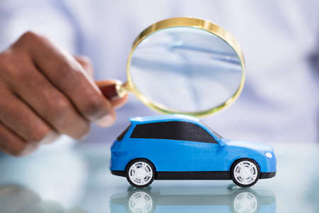 Close-up de la mano de una persona sosteniendo una lupa mirando coche de juguete azul