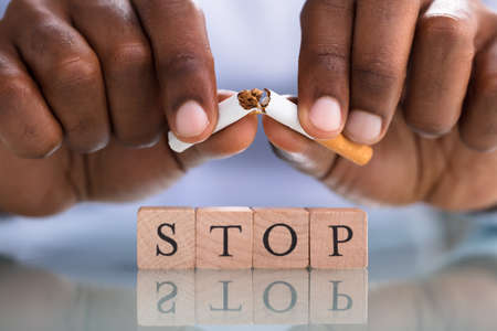 Close-up Of A Person's Hand Breaking Cigarette Over The Stop Blocks On The Reflective Desk