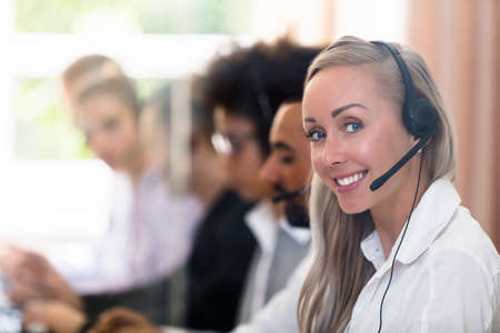 Portrait Of A Happy Young Female Customer Service Executive Standard-Bild
