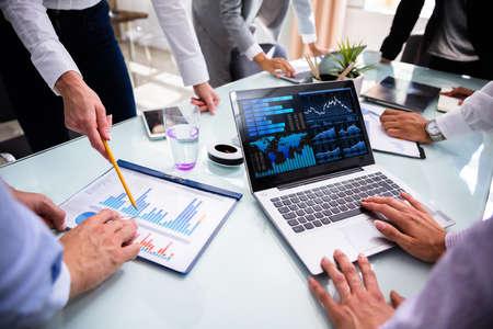 Geschäftsleute, die Laptop beim Analysieren von Diagrammen bei Besprechungen verwenden Standard-Bild