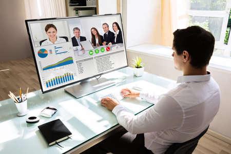 Videoconferencia de joven empresario con sus socios en la computadora