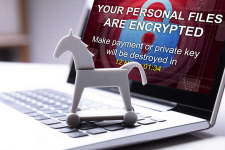 Close-up Of Trojan Horse Icon And Laptop Screen Showing Personal Files Encrypted Stock Photo